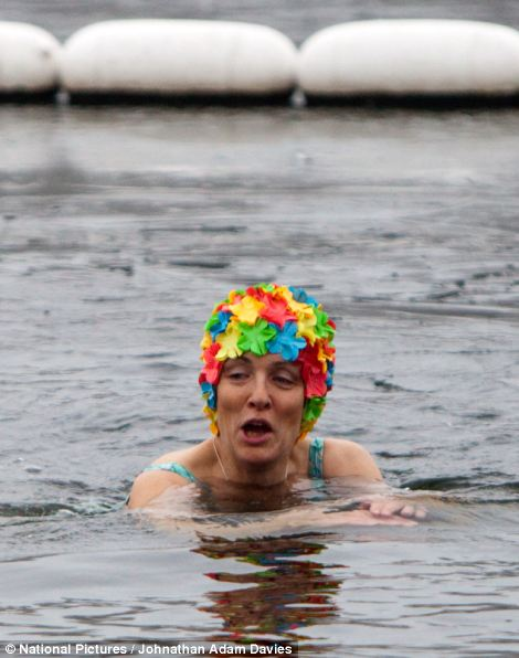Members of the Serpentine Swimming Club brave the ice covered water for an early morning dip in the Serpentine in Hyde Park as temperatures hover around freezing
