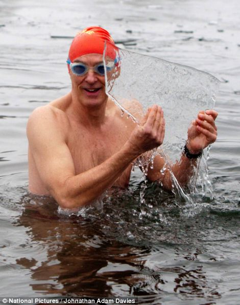 Rod Ewing of the Serpentine Swimming Club holds up a piece of ice in the Serpentine
