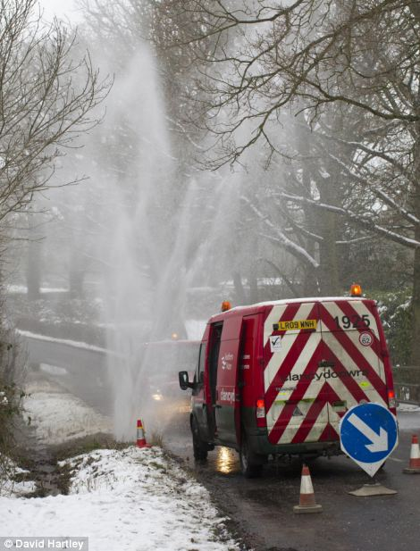 Water spurts into the air after the cold weather has caused a water main pipe to burst at Goose Hill, Newbury, Berkshire