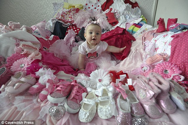 'Little miracle': Baby Princess Tiiaana surrounded by some of her clothes, which include Baby Dior ballet flats and KP sleepsuits designed by her mother's idol Katie Price