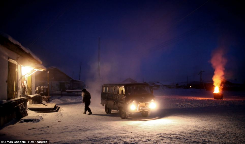 A man leaves his  van and walks into Oymyakon's only shop
