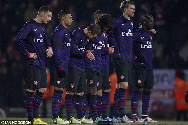 Anxious: Arsenal players await their fate in the penalty shootout against Bradford