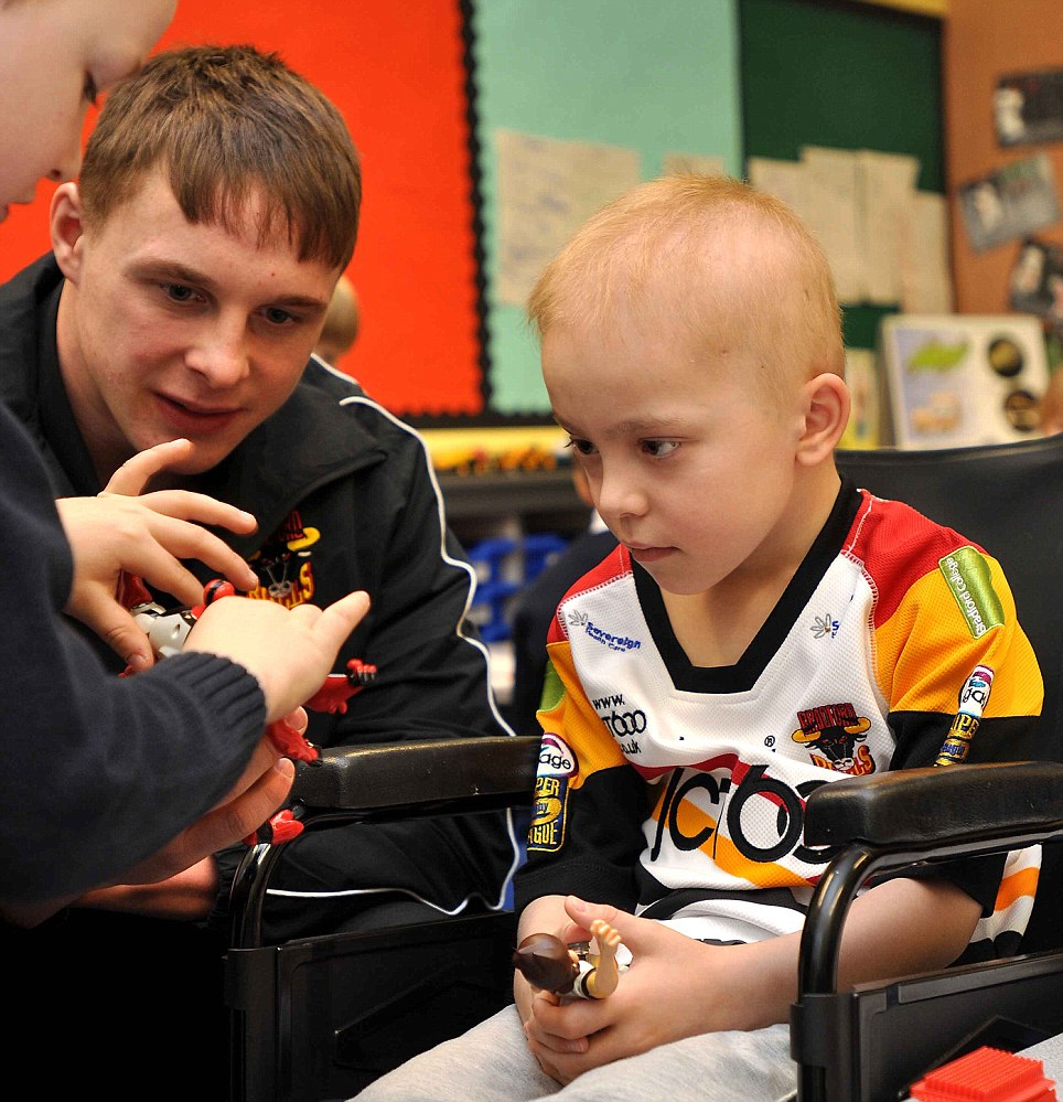 Tough cookie: Jake meets Bradford Bulls player James Donaldson (left) during a surprise visit from the rugby league club to his St Paul's Primary School three years ago