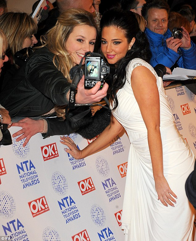 Say cheese: After doing her bits for the professional cameras Tulisa stopped to take photos with fans