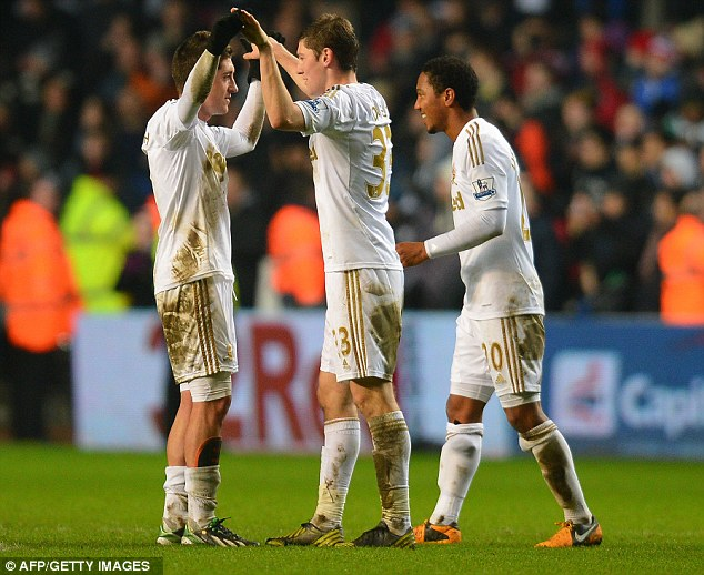 Job done: Swansea celebrate at the final whistle