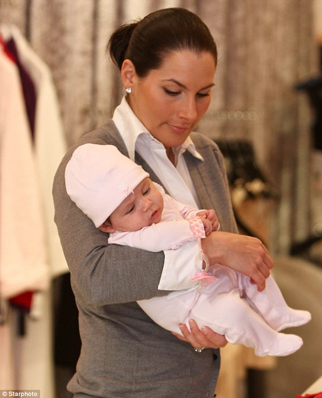 Bundle of joy: Former Eliot Spitzer call Ashley Dupré was pictured today at her store in Red Bank, New Jersey with baby Izabel