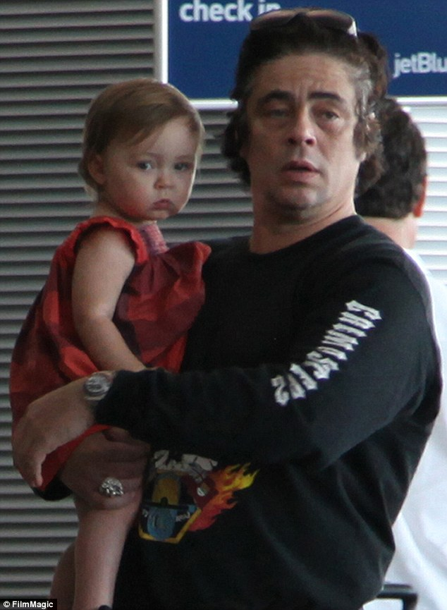 Spitting image: Benicio Del Toro cuddles his daughter Delilah as they leave Puerto Rico after the one-year-old was reportedly baptised over the New Year