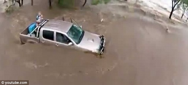 Deluged: Two women, one holding a small child, are seen stranded in their flooded truck, waiting for help