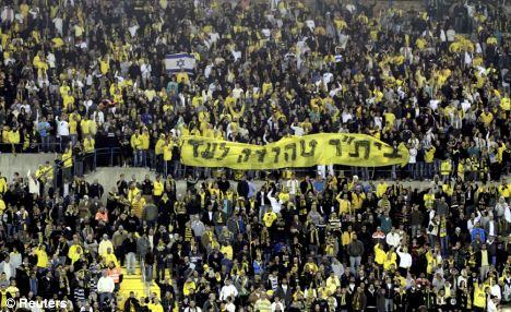 Beitar Jerusalem fans hold a banner reading 'Beitar will always remain pure'