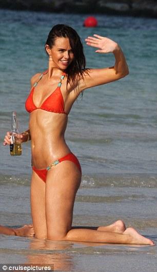 Having a blast: Jennifer waved to other holidaymakers as she enjoyed a bottle of Corona