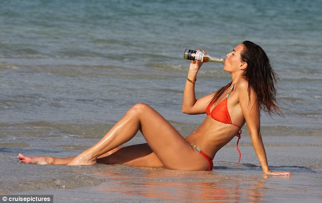 Taking it easy: Jennifer took to the waters at the Le Royal Meridien Beach Resort and Spa with a beer in hand