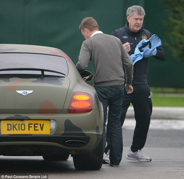 Signed and sealed? Man City coach Bran Kidd rushed over to Balotelli to get a shirt signed after training today