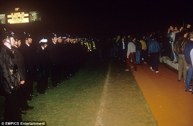 Thin blue line: Police officers try to clear the pitch as Millwall fans try to encroach. The scoreboard in the background warns that the players will not return until the playing surface is clear