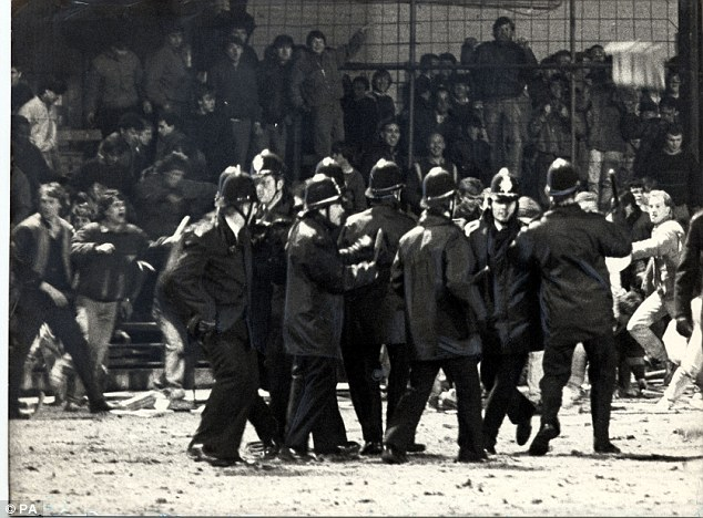 Riot: Police with batons drawn fight with hooligans on the pitch after the final whistle
