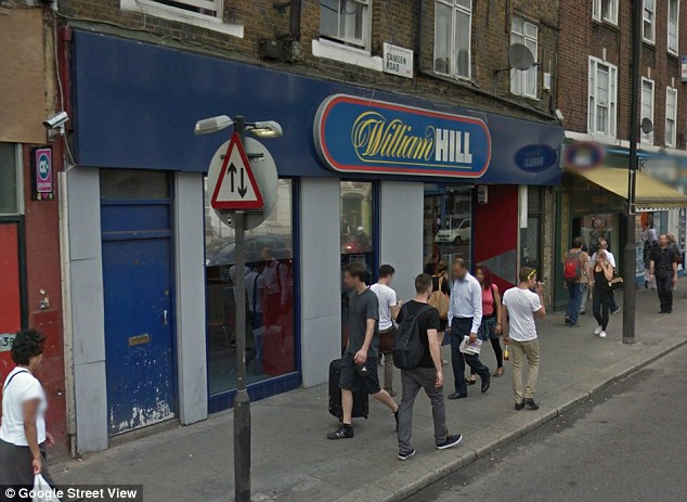 Tragic: The young victim was walking past this William Hill bookmakers, pictured with its hoarding in place, in Camden Road just before 5pm today