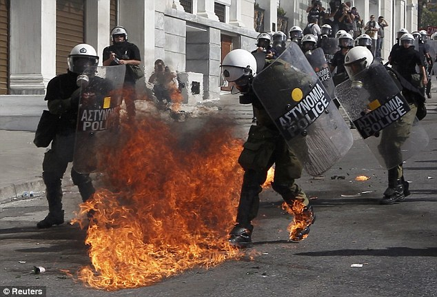 Anger: Flames from a molotov cocktail flare up near Greek riot police at a protest march against cuts in October