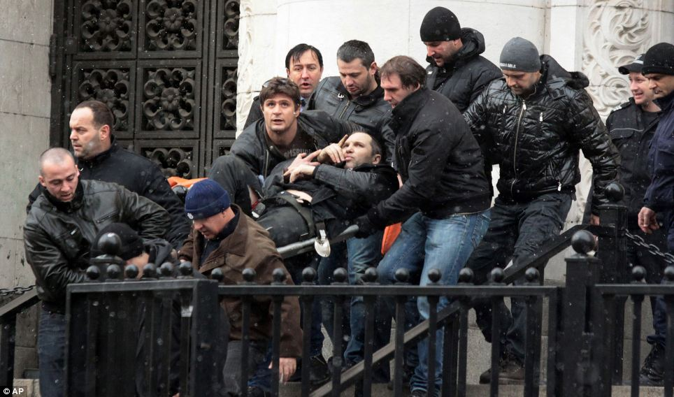 Wounded: Guards carry Zlatomir Ivanov (aka Zlatko Baretata) to safety after he was gunned down in front of the City Court in Sofia