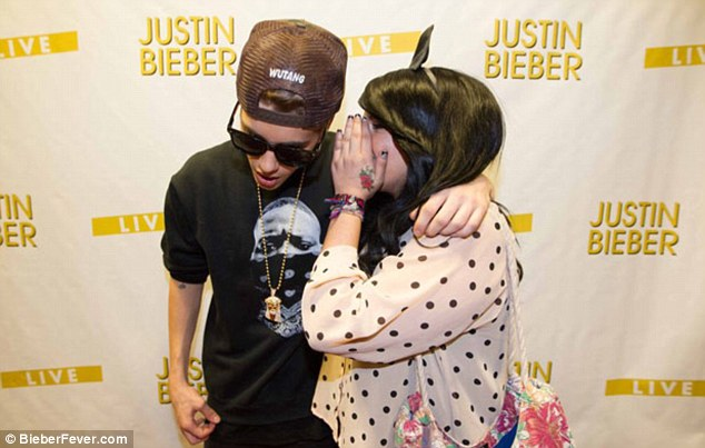 That's better: After posing for the picture Bieber then put his arm around the girl as she whispered into his ear