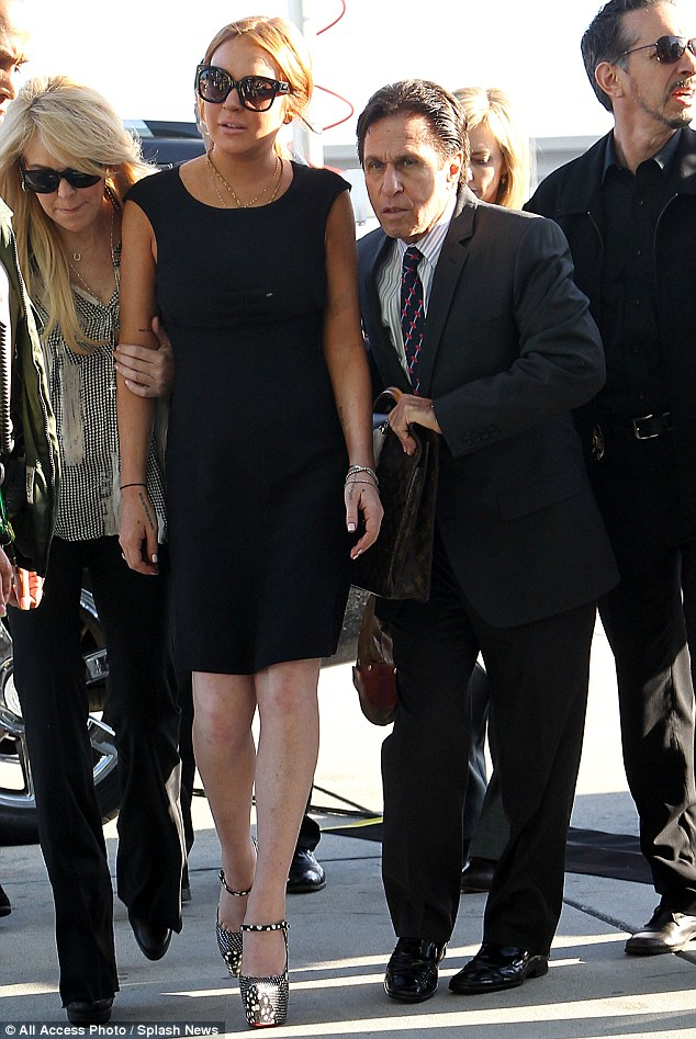 Flanked: Lindsay was flanked by her mother and her lawyer Mark Heller as she arrived in court on Wednesday