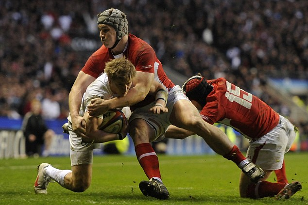Body on the line: Halfpenny helps halt Strettle before Wales lifted the Triple Crown (below)