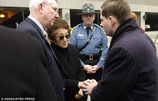 Closure: The professor's widow Tesuk Im (center left) is consoled by University of Missouri police chief Jack Watring (left) and highway patrol commander Captain Dale Schmidt (right)