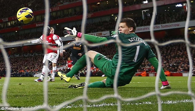 Net gains: The Liverpool striker scores against Arsenal stopper Wojciech Szczesny on Wednesday night