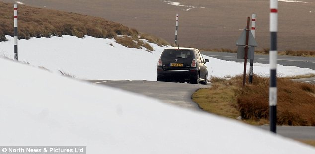 Disruption: A motorist driving past snow-covered banks in the North East today