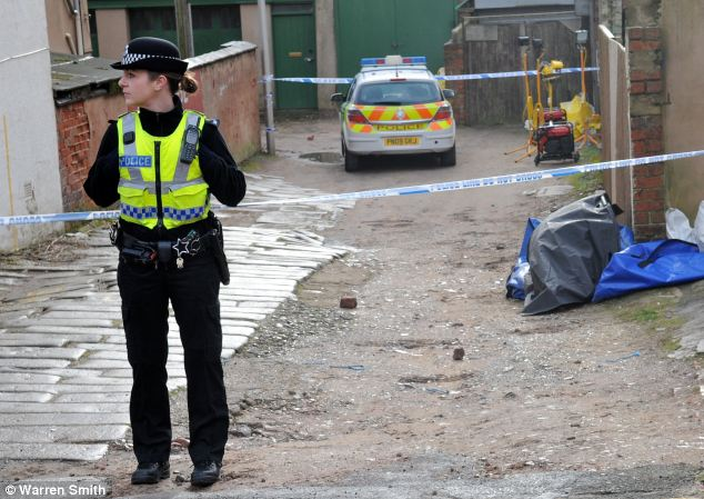 A police officer guards the alleyway scene where a schoolgirl's body was found burning