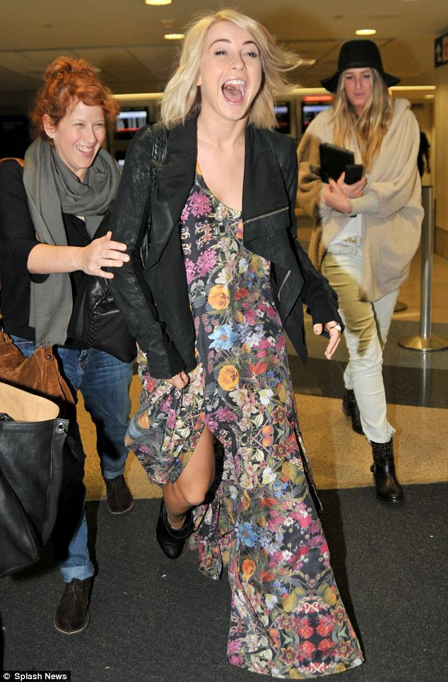 Happy go lucky: Julianne looked really happy as she arrived at LAX on Saturday