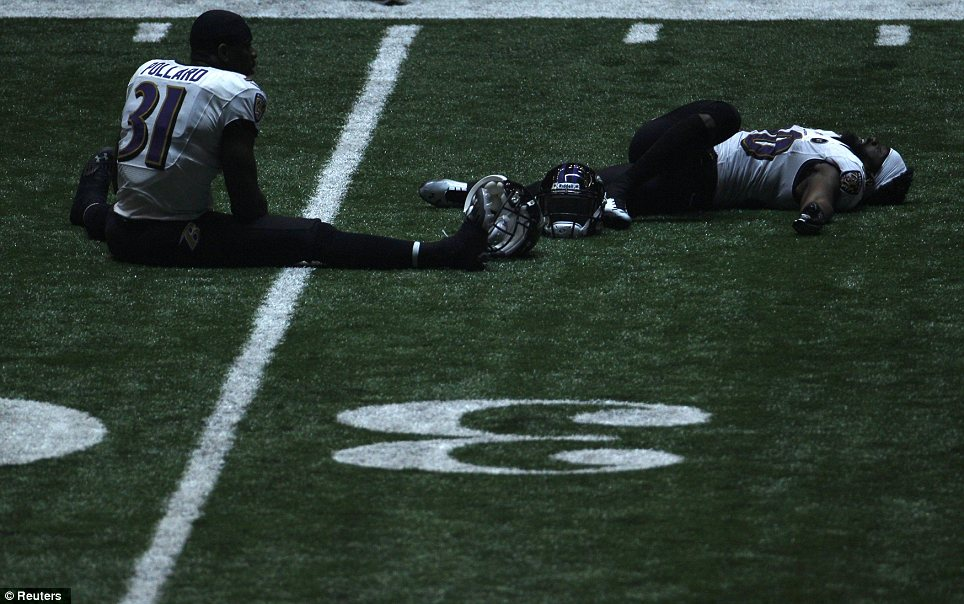 Staying warm: Baltimore Ravens strong safety Bernard Pollard and free safety Ed Reed sit on the turf stretching during the power outage