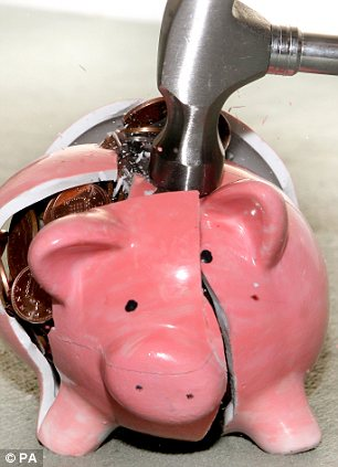 A piggy bank being smashed by a hammer