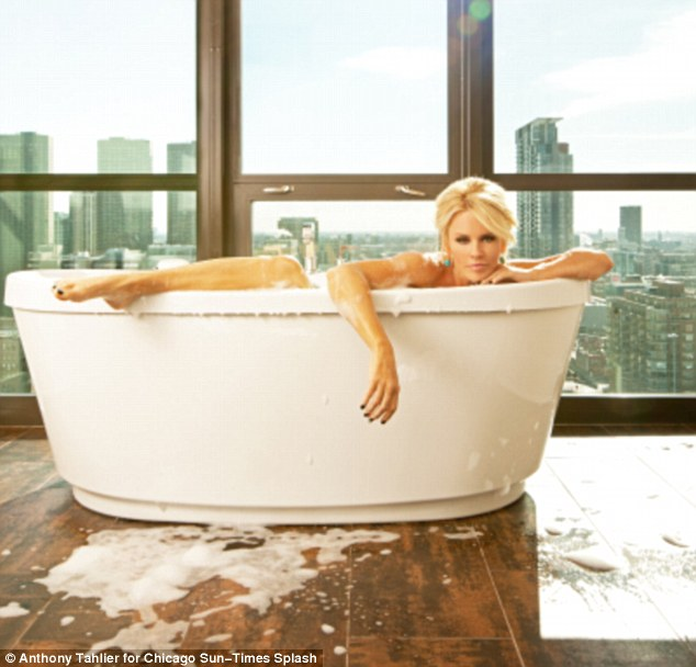 Provocative: The former Playboy star straddles the edge of the tub with her leg in one frame, spilling water and bubbles all over the floor of her Chicago apartment