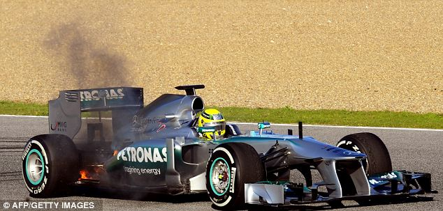 Mercedes' German driver Nico Rosberg stops his car as it burns during a training session