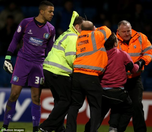 Idiot: The Gillingham supporter was dragged away by stewards