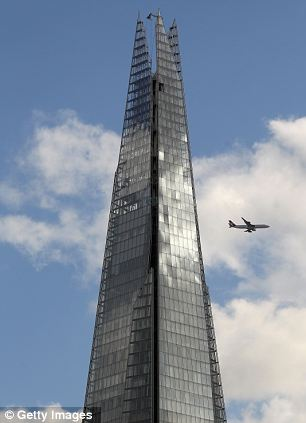 An aeroplane flies past the newly-opened Shard skyscraper in London, the tallest building in Europe