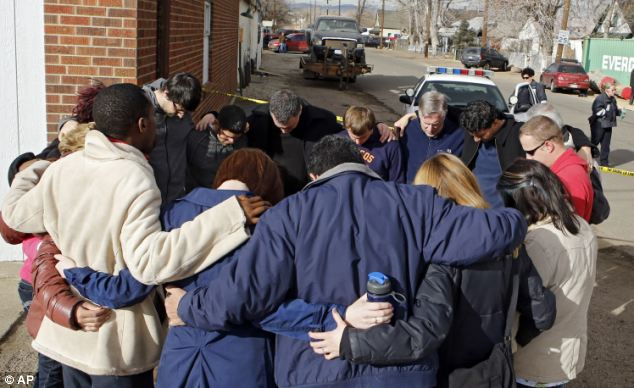 Members of a community church gather in a prayer circle a block from where Mayra Nunez and two of her children were found dead