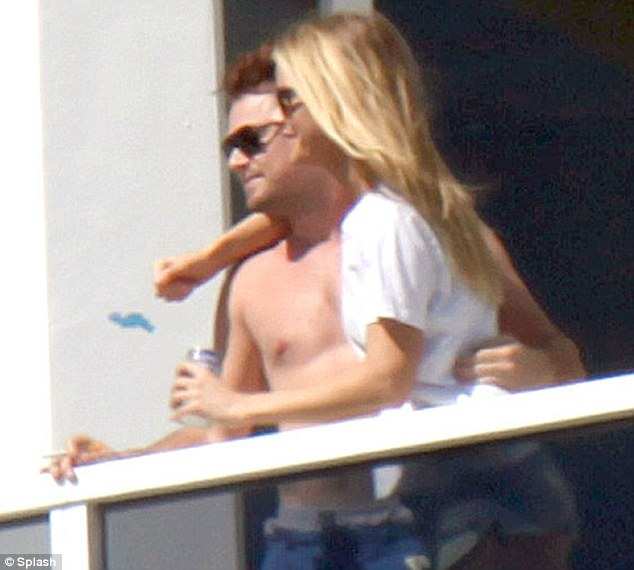 Getting cosy: Leonardo DiCaprio was spotted with a mystery blonde woman draped over him as he relaxed on his hotel balcony in Miami