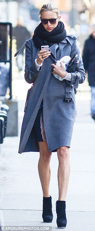 Winter chic: The supermodel wrapped up in an effortlessly chic grey wool coat, which she teamed with towering shoe boots, a cosy snood and shades