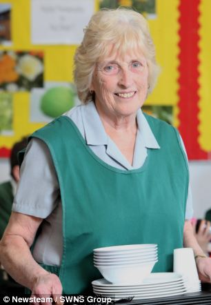 The uniform has changed but the smile remains the same for Britain's longest-serving dinner lady Julie Barrick, 75