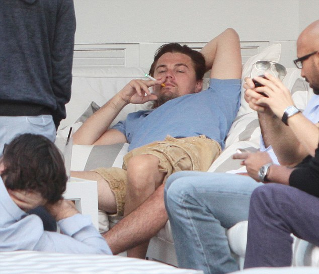 Life of leisure: The A-lister seems completely relaxed as he hangs out with friends, puffing on what looks like an electronic cigarette