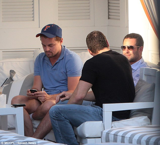 Glued to his phone: The A-lister can't seem to tear himself away from his phone as his friends chat around him