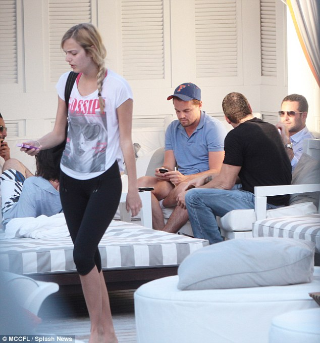 New blonde companion: DiCaprio checks his phone after another blonde woman gives him an affectionate kiss in Miami on Wednesday
