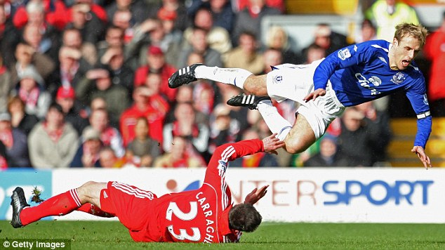 Tough tackling: Strong challenges and a competitive edge have been a trademark feature of Carragher's 700-plus game career. Here, he sends Phil Neville flying during the 2008 Merseyside derby