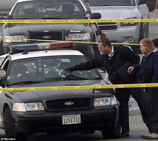 Riddled with bullets: LAPD inspects one of their police cars that was allegedly shot up by Dorner during a chase early today