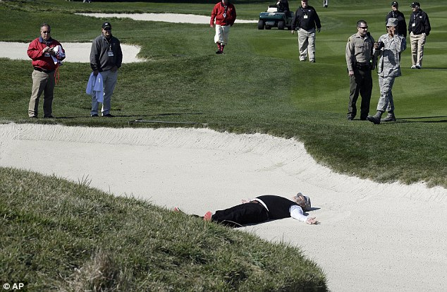 Comedian: Murray makes a sand angel in a bunker on the second hole