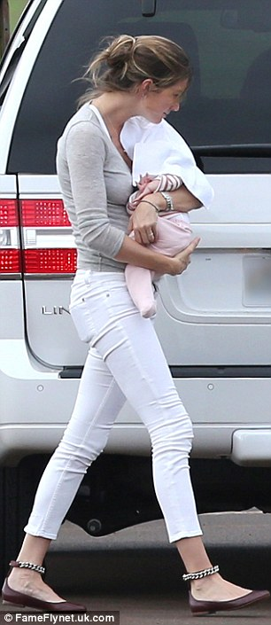 Casually does it: Gisele wore skinny white jeans and a grey top as she arrived for her sunshine break