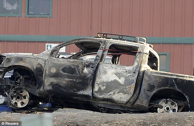 Getting closer: Police are searching Dorner's burned out truck for any potential clues