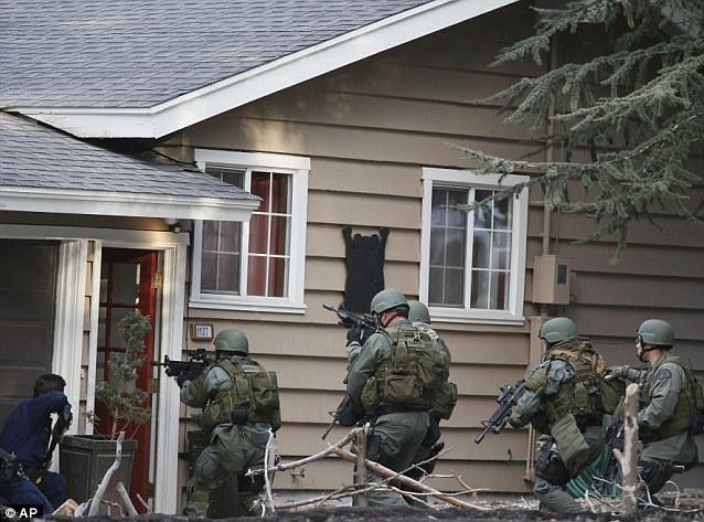 Door-to-door: A SWAT team barrels into a home in Big Bear, Calif. in search of shooting suspect Christopher Dorner