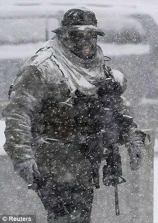 Bundled up: A Los Angeles county sheriff SWAT member prepares to continue the search for Christopher Dorner in the heavy snow at the Bear Mountain ski resort
