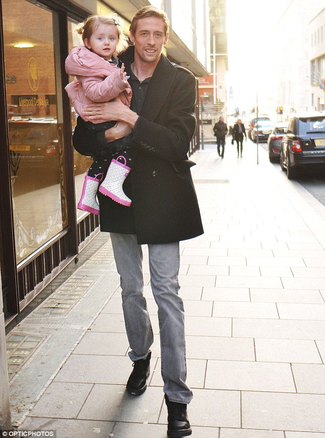 Daddy's girl: The Stoke City footballer carries his little girl after she gets tired of walking